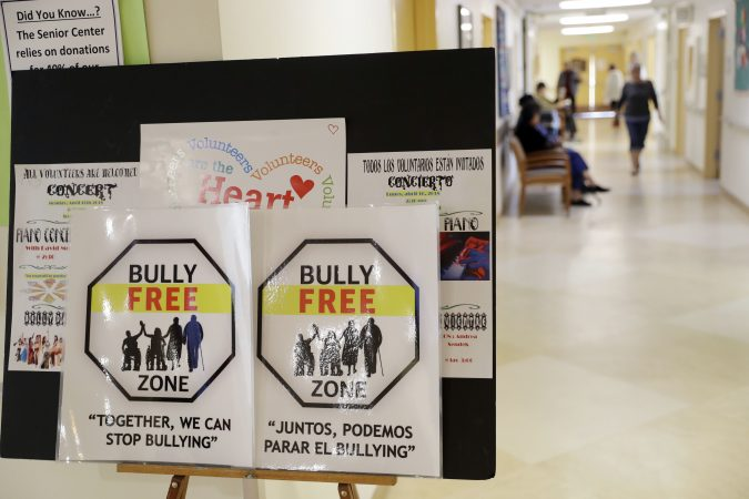 In this Friday, April 13, 2018 photo, signs promote a bully-free environment at the On Lok 30th Street Senior Center in San Francisco. After problems at the facility, all staff members received 18 hours of training that included lessons on what constitutes bullying, causes of the problem and how to manage such conflicts. Seniors were then invited to similar classes teaching them to alert staff or intervene themselves if they witness bullying. (Marcio Jose Sanchez/AP Photo)