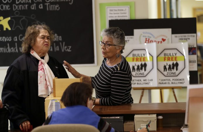 In this Friday, April 13, 2018 photo, two women talk in front of anti-bullying signs at the On Lok 30th Street Senior Center in San Francisco. After problems at the facility, all staff members received 18 hours of training that included lessons on what constitutes bullying, causes of the problem and how to manage such conflicts. Seniors were then invited to similar classes teaching them to alert staff or intervene themselves if they witness bullying. (Marcio Jose Sanchez/AP Photo)