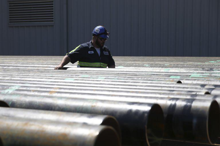 William Hampton walks between steel pipes at the Borusan Mannesmann plant in Baytown, Texas, Monday, April 23, 2018.  (AP Photo/Loren Elliott)