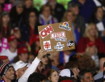 An audience member holds a fake news sign during a President Donald Trump campaign rally in Washington Township, Mich., Saturday, April 28, 2018.