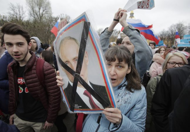 Demonstrator carries a poster depicting Russian President Vladimir Putin during a massive protest rally in St.Petersburg, Russia, Saturday, May 5, 2018. Alexei Navalny, anti-corruption campaigner and Putin's most prominent critic, called for nationwide protests on Saturday, two days ahead of the inauguration of Vladimir Putin for a fourth term as Russian president. (Dmitri Lovetsky/AP Photo)