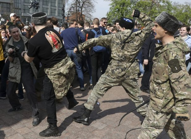 Fighters of National Liberation movement clash with protesters during clashes at a demonstration against President Vladimir Putin in Pushkin Square in Moscow, Russia, Saturday, May 5, 2018.  Russians angered by the impending inauguration of Vladimir Putin to a new term as the country's president demonstrated throughout the country on Saturday. Police arrested hundreds, including protest organizer Alexei Navalny, the anti-corruption campaigner who is Putin's most prominent foe. (AP Photo)