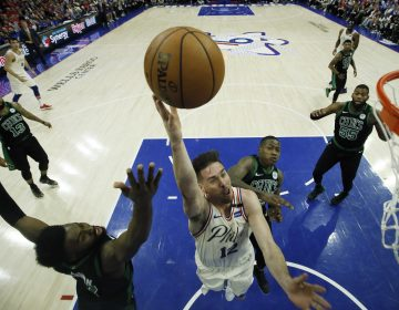 Philadelphia 76ers' T.J. McConnell, center, goes up for a shot against Boston Celtics' Jaylen Brown, left, and Terry Rozier during the second half of Game 4 of an NBA basketball second-round playoff series, Monday, May 7, 2018, in Philadelphia. (AP Photo/Matt Slocum)