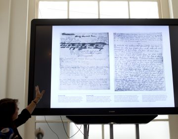 A video shows the text underneath two taped off pages from Anne Frank's diary during a press conference at The Anne Frank Foundation's office in Amsterdam, Netherlands, Tuesday, May 15, 2018. Left standing is the foundation's director Ronald Leopold. (Peter Dejong/AP Photo)
