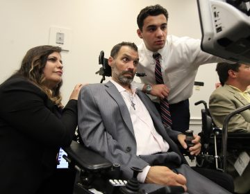 ALS patient Frank Mongiello communicates with his wife, Marilyn, and his son during a news conference following the passage of the