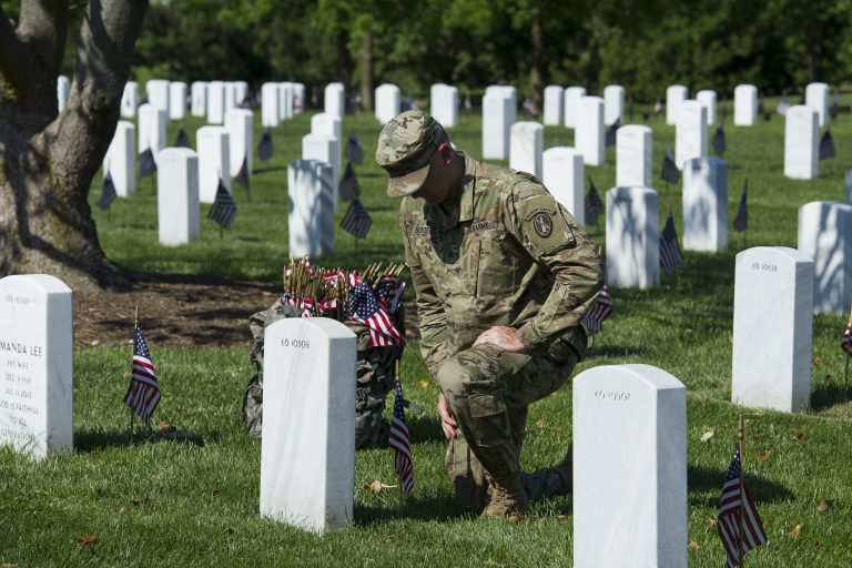 A member of the Army 3d U.S. Infantry Regiment, The Old Guard, pauses to honor a fallen soldier while places flags a the gravesite of the nation's fallen military heroes during its annual Flags In ceremony at Arlington National Cemetery, Thursday, May 24, 2018, in Arlington, Va. (AP Photo/Cliff Owen)