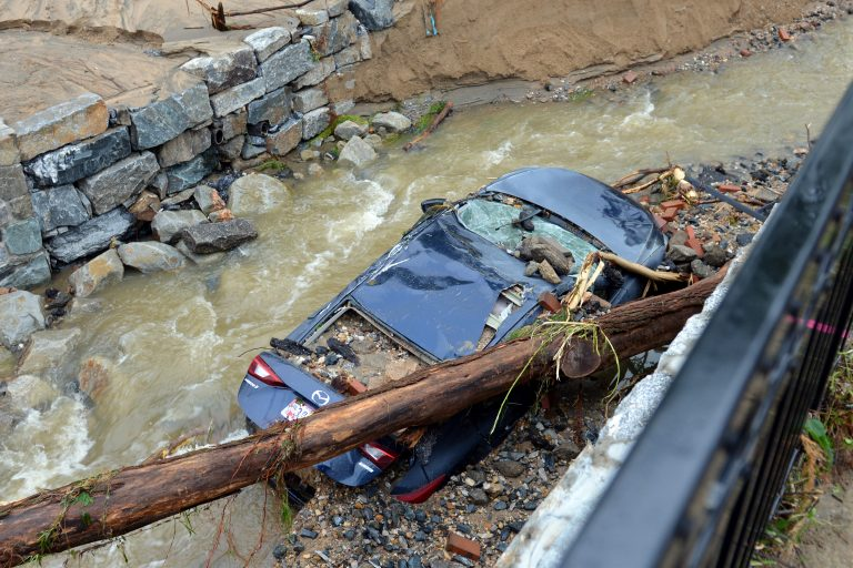 Water moves past a car swept into the riverbank and smashed by a fallen tree is shown just off Main Street in flood-ravaged Ellicott City, Md., Monday, May 28, 2018. Sunday's destructive flooding left the former mill town heartbroken as it had bounded back from another destructive storm less than two years ago. (AP Photo/David McFadden)