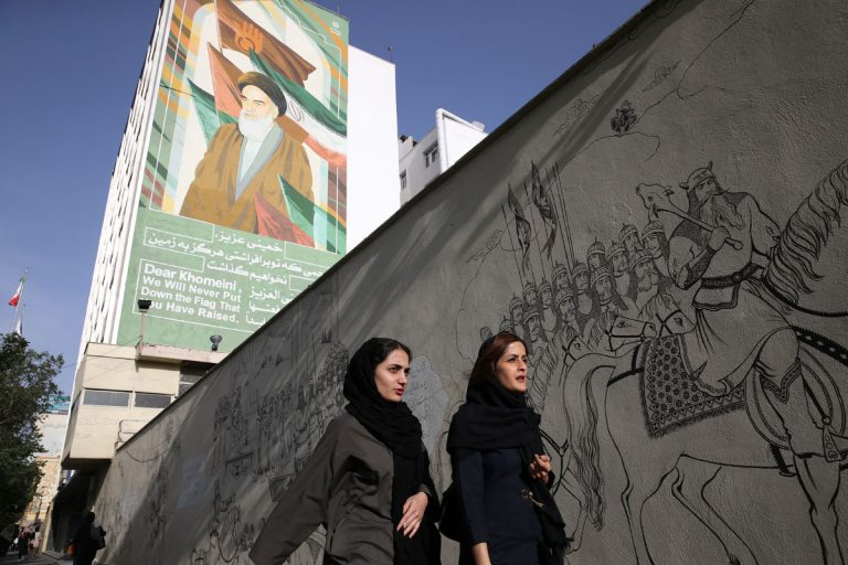 Iranian women walk past a portrait of the late revolutionary founder Ayatollah Khomeini and paintings of Persian poetry in Tehran, Iran, Monday, May 7, 2018. (Vahid Salemi/AP Photo)