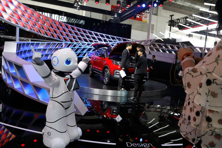 In this April 26, 2018, photo, a robot entertains visitors at the booth of a Chinese automaker during the China Auto 2018 show in Beijing, China. Under President Xi Jinping, a program known as