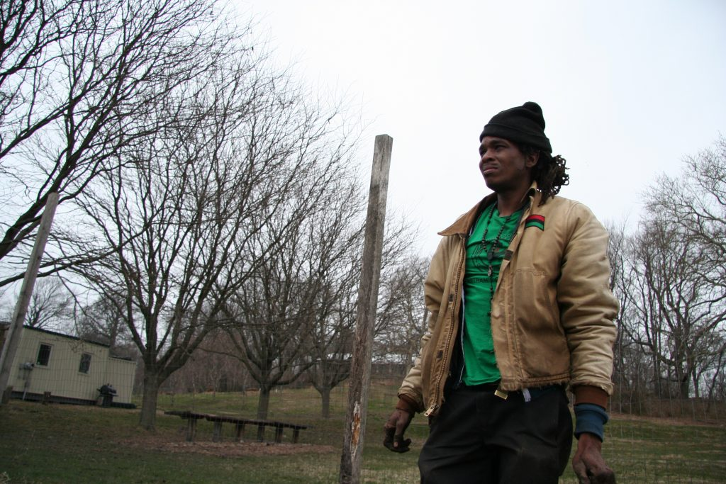 Chris Bolden-Newsome stands and looks out at the Sankofa Community farm. He farms using natural farming techniques passed on to him from his parents and grandparents. (Alan Yu/WHYY)