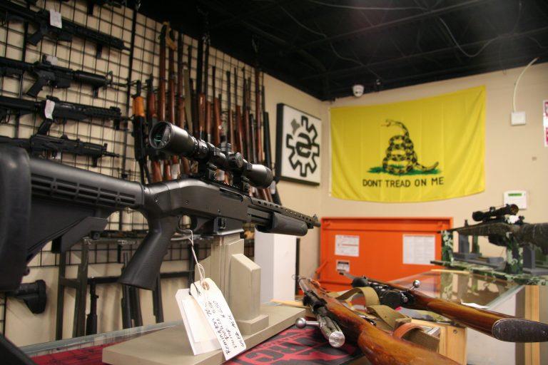A display of rifles in a gun shop, with a flag that says