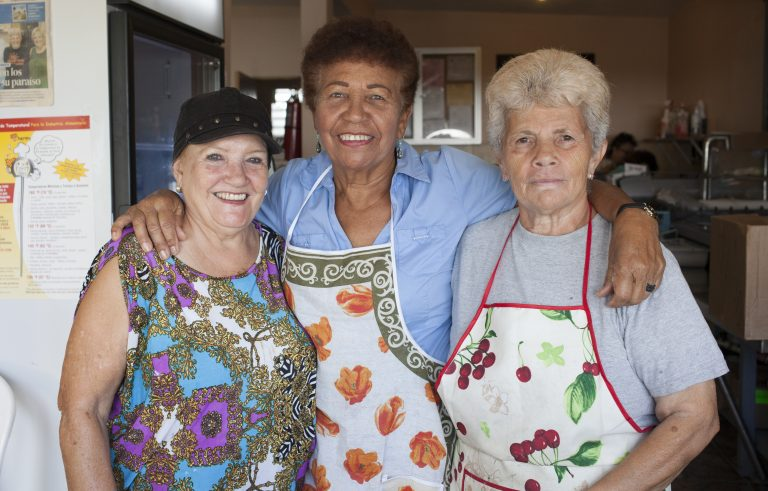 A group of women in the community of Mariana, in Puerto Rico, meet everyday to cook for their neighbors. They say after the storm, the work and camaraderie have eased depression. (Irina Zhorov/WHYY)