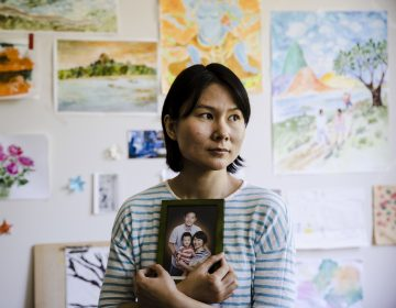 Hua Qu, the wife of Chinese-American Xiyue Wang, poses with a portrait of her family in Princeton, N.J., on May 9. Families of Americans detained in Iran are hoping President Trump's decision to withdraw from the Iran nuclear deal will not make it harder to get their love ones freed. (Matt Rourke/AP)