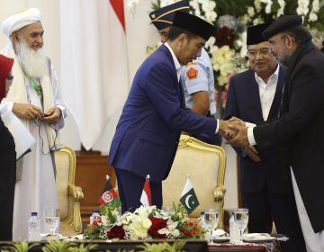 Scholars from Afghanistan, Pakistan and Indonesia attended a conference on Friday to discuss stability in Afghanistan. Indonesian President Joko Widodo (center) shakes hands with Qibla Ayaz, chairman of Pakistan's Council of Islamic Ideology. (Dita Alangkara/AP)