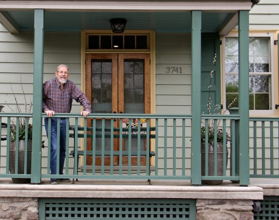 Photographer Bruce Katsiff stands on the front porch of the Lumberville General Store. (Emma Lee/WHYY)