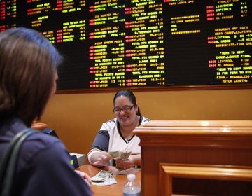 Crystal Kalahiki pays out a bet in the sports book at the South Point hotel-casino, Monday, May 14, 2018, in Las Vegas. The Supreme Court on Monday gave its go-ahead for states to allow gambling on sports across the nation, striking down a federal law that barred betting on football, basketball, baseball and other sports in most states. (AP Photo/John Locher)