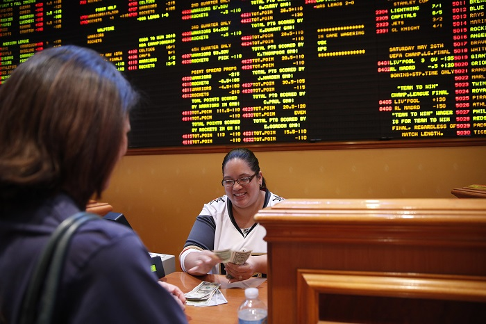 Crystal Kalahiki pays out a bet in the sports book at the South Point hotel-casino, Monday, May 14, 2018, in Las Vegas. The U.S. Supreme Court gave its go-ahead for states to allow gambling on sports across the nation, striking down a federal law that barred betting on football, basketball, baseball and other sports in most states. (John Locher/AP Photo)