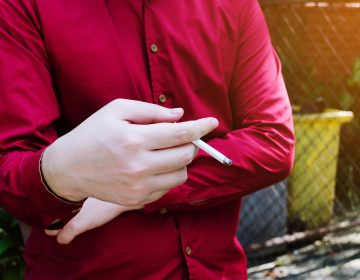 A man in a red shirt holds a lit cigarette in his right hand