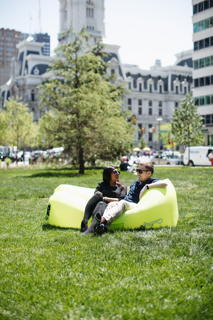 City employees Surj Jones and Josh Lippert lounging on the LOVE lawn during  lunchtime. May 7, 2018 (Neal Santos for PlanPhilly)