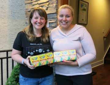 Johanna Humphrey, (left), ended up with 24 boxes of crayons she didn't need. She gave them to teacher Laura Smith, (right), through the Buy Nothing Project. It encourages people to share without money changing hands. (Jeff Brady/NPR)