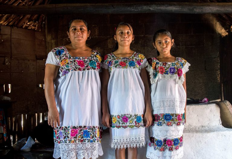 Maria de los Angeles Tun Burgos with daughters Angela, 12, and Gelmy, 9, in their family home in a Maya village in Yucatan, Mexico. (Adriana Zehbrauskas for NPR)