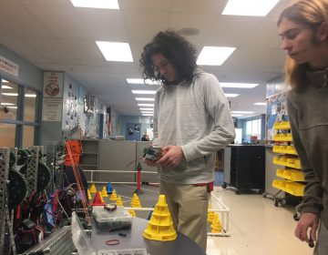 Dickinson High junior Jeremy Nolan works on his robot as partner Ian Shotwell observes. (Cris Barrish/WHYY)