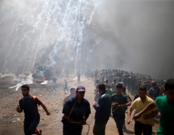 Palestinian demonstrators run from tear gas fired by Israeli troops during a protest against the U.S. embassy move to Jerusalem and ahead of the 70th anniversary of Nakba, at the Israel-Gaza border east of Gaza City.