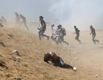 Palestinian demonstrators run or take cover from tear gas fired by Israeli forces at the Israel-Gaza border. (Ibraheem Abu Mustafa/Reuters)