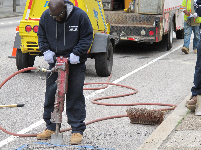 Water Department crews jackhammering open a street.