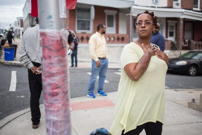 Malika Lovelace, who works for the Philadelphia Anti-Drug/Anti-Violence Networ,k looks at a makeshift memorial at the site where 17-year-old Sandrea Williams was shot to death in her mother's West Philadelphia neighborhood. (Emily Cohen for WHYY)