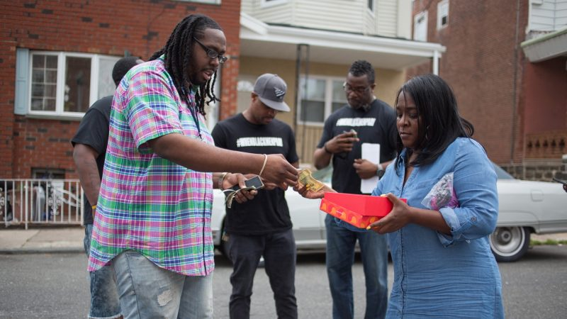 """Tanya Parnell, or Miss Tee as the neighborhood kids call her, sells buttons with a photograph of Sandrea Williams and """"#JusticeforSandrea"""" written on it. The proceeds will go directly to the 17-year-old's family. (Emily Cohen for WHYY)"""