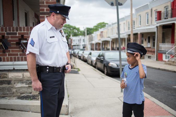 Sergeant Frank Kelly, of the 19th district, plays with Swyhir Crew, 7, who was inside his home down the street from where his teenage cousin and another boy were shot and his neighbor, 17-year-old Sandrea Williams, was killed on May 11, 2018. (Emily Cohen for WHYY)