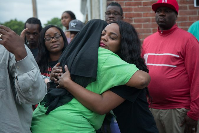 Naisha Rhoden, Sandrea's aunt, gives a hug to Movita Johnson-Harrell, after she gave a speech to the gathered crowd about how she became an activist after her son was murdered in a drive-by act of mistaken identity. (Emily Cohen for WHYY)