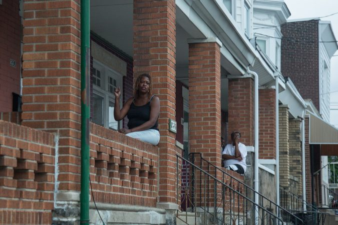 Neighbors gather from their porches to support the rally the bring justice for the death of Sandrea WIlliams who was shot to death outside of her mother's home in West Philadelphia on May 11th, 2018. You can see the corner where she and two other boys were shot at from the porches that line the neighborhood. (Emily Cohen for WHYY)