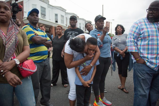 Sakinah Crew comforts her 7 year old son, Swyhir, during a rally to bring justice for the death of Sandrea Williams. She was killed in a random act of gun violence outside of her mother's home in West Philadelphia. Their teenage cousin was also injured by gunfire that night. (Emily Cohen for WHYY)