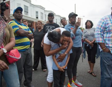 Sakinah Crew comforts her 7-year-old son, Swyhir, during a rally to bring justice for the killing of Sandrea Williams. She was killed in a random act of gun violence outside of her mother's home in West Philadelphia. Their teenage cousin was also injured by gunfire that night. (Emily Cohen for WHYY)