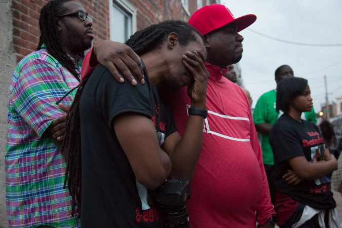 Marlando Powell finds comfort in a community member at a vigil for his 17 year old niece Sandrea Williams three weeks after she was shot and killed in a random act of gun violence in front of her mother's home. The vigil doubled as a rally to bring justice to her family. (Emily Cohen for WHYY)