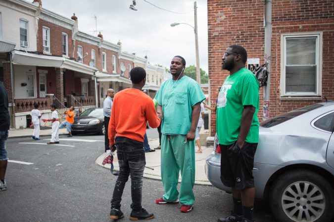 Amir hosendorf, who works at St Christopher's Hospital and lives in neighborhood, greets a friend at the rally bring justice for the death of 17 year old Sandrea Williams three weeks after she was gunned down in a random act of violence outside of her mother's in their West Philadelphia home on May 11th 2018. (Emily Cohen for WHYY)