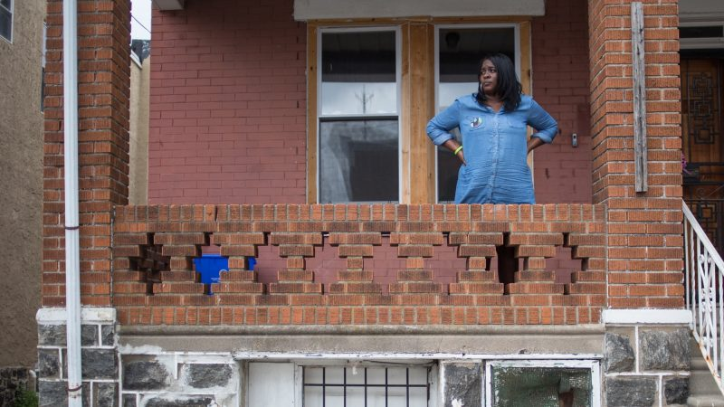 Tanya Parnell, or Miss Tee as the neighborhood kids call her, stands on her porch which is next to Sandrea Williams' mother's home and overlooks the corner in which the 17 year old girl was murdered in a random act of violence three weeks earlier. (Emily Cohen for WHYY)