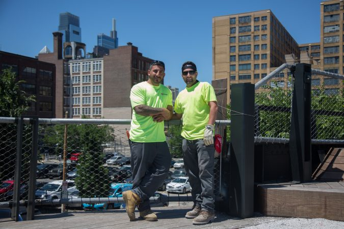Giuseppe Giambanco (left) and James Postiglione, of AP Construction, make some final touches on the park they helped build June 14th 2018. (Emily Cohen for WHYY)