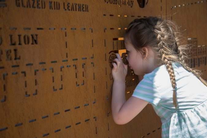 Cecilia Norris, 3, takes a peek through the cutouts in the iron picture map of the city of Philadelphia that greets visitors as they enter the first phase of the Philadelphia Rail Park June 14th 2018. (Emily Cohen for WHYY)