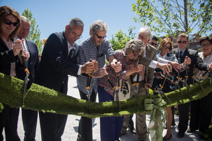 "Integral members of the team that brought the rail park to life, including Sarah McEneaney (center) and John Struble (center left), cut the ""green"" ribbon, officially opening the first quarter mile of the Philadelphia Rail Park June 14th 2018. (Emily Cohen for WHYY)"