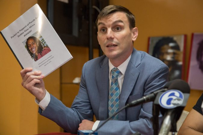 Brad Thomson, a Chicago-based lawyer, holds up the thick packet of letters of support for Debbie Africa's that were presented to the parole board. (Emily Cohen for WHYY)