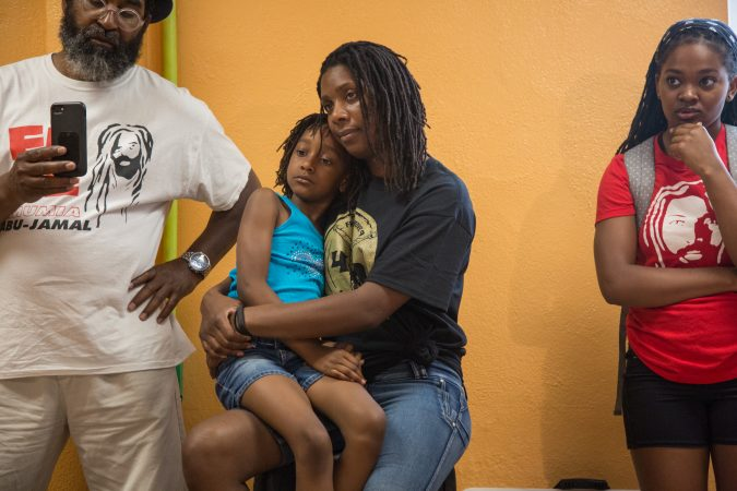 Robin Africa holds her daughter, Alia, 6, at the first public appearance of Debbie Africa since being released from prison after 39 years and 10 months. (Emily Cohen for WHYY)