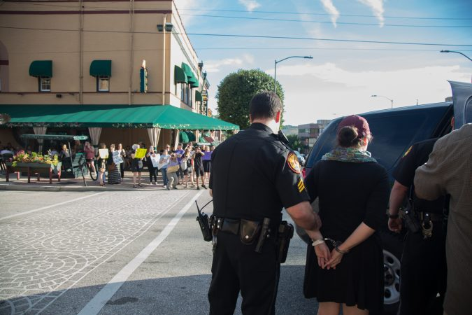 Protester Cathrine Coll of Lansdowne is led away in handcuffs after she refused to leave the fundraising event for Pennsylvania state Sen. Daylin Leach. (Emily Cohen for WHYY)