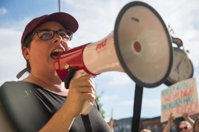 Cathrine Coll leads chants Thursday evening at a protest outside of a Pennsylvania state Sen. Daylin Leach fundraising event in an attempt to bring attention to accusations of sexual harassment against him. (Emily Cohen for WHYY)