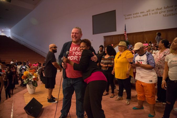 Minister Justin Gonzalez and Maria Caldwell hug after a successful final rehearsal for a gospel concert at Independence Hall as part of this year's Wawa Welcome America celebration. (Emily Cohen for WHYY)