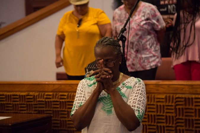 A member of the chorus bows her head as a prayer is said before the choir's final rehearsal begins. (Emily Cohen for WHYY)