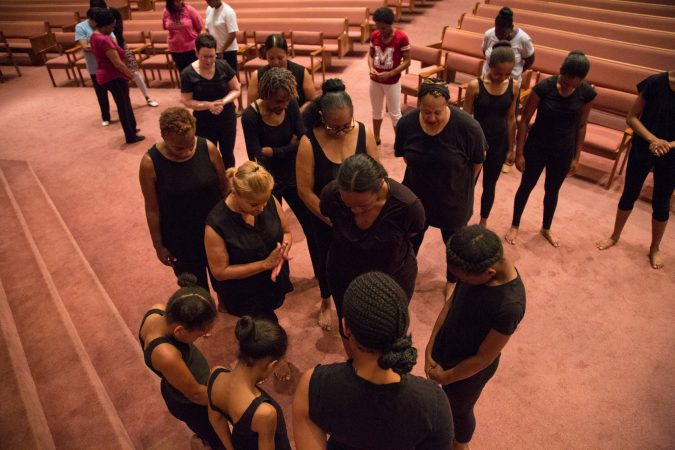 Members of the Praise Dancers bow their heads in prayer at the beginning of their final rehearsal. (Emily Cohen for WHYY)