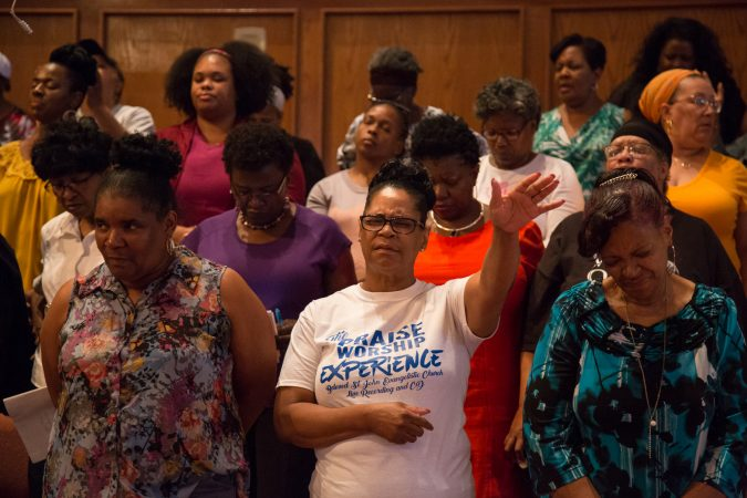 Members of the chorus bow their heads in prayer as one is said at the beginning of their final rehearsal. (Emily Cohen for WHYY)